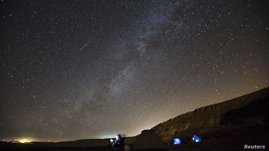 FILE - A meteor streaks across the sky in the early morning as people watching during the Perseid meteor shower in Ramon Carter near the town of Mitzpe Ramon, southern Israel, August 13, 2015.