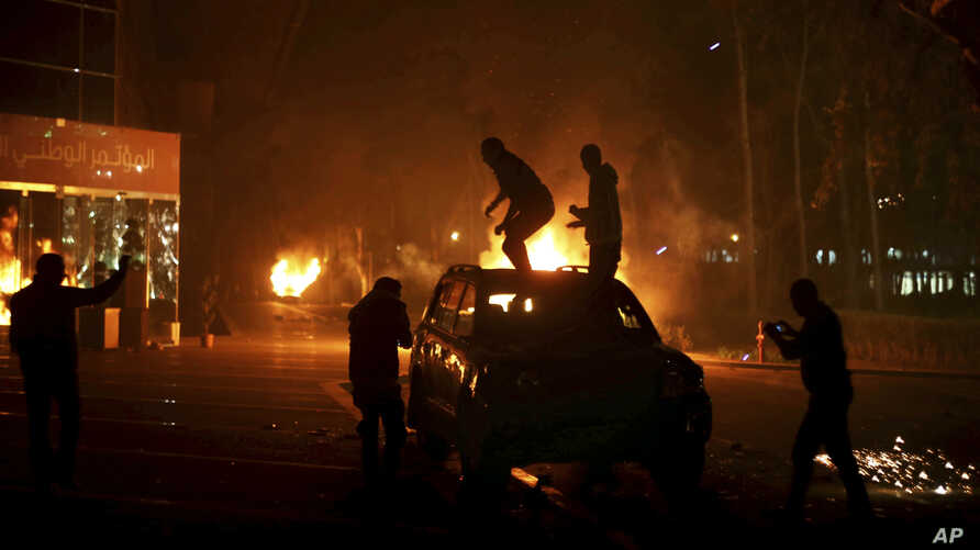 FILE -Protesters stand atop a vehicle as others burn in front of the National Conference Hall, in Tripoli, Libya, March 2, 2014, in this photo by photographer and video journalist Mohamed Ben Khalifa, who was killed in Libya on Jan. 19, 2019.