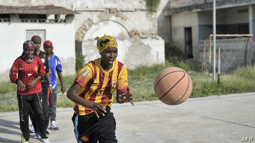 A girl passes a ball during a drill at basketball training session in Mogadishu, Somalia, July 6, 2013.