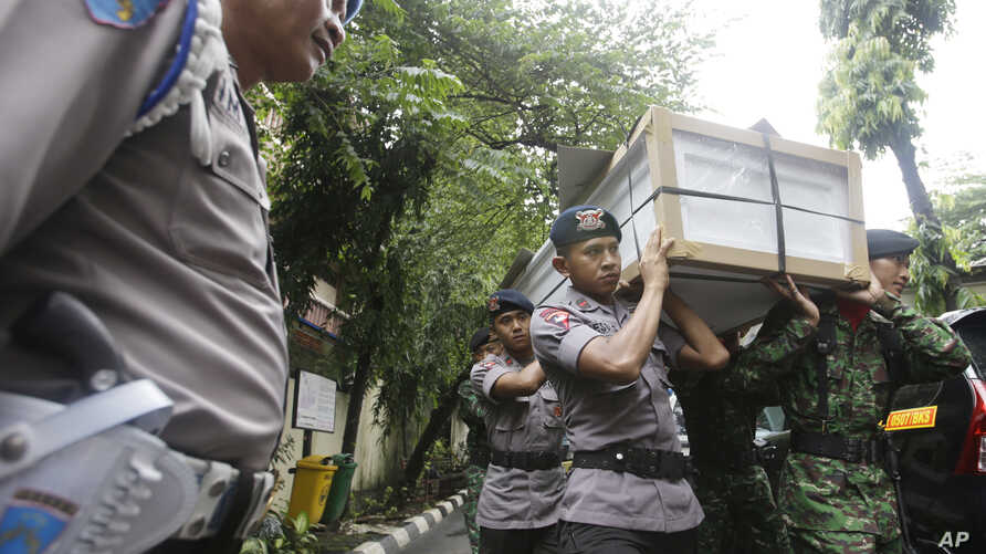 Indonesian police officers and soldiers carry one of the coffins prepared for the victims of a military helicopter which crashed in Poso, Central Sulawesi, at hospital in Jakarta, Indonesia, March 21, 2016.