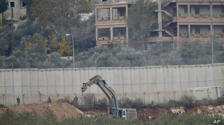 """Israeli military digger works on the border with Lebanon in the northern Israeli town of Metula, Tuesday, Dec. 4, 2018. The Israeli military launched an operation on Tuesday to """"expose and thwart"""" tunnels built by Hezbollah it says stretch from Leban"""