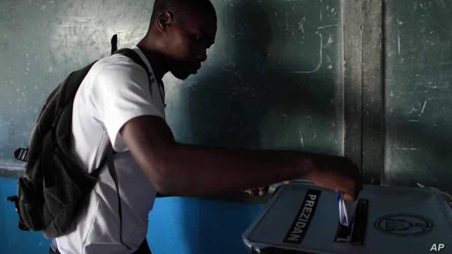 A man casts his ballot at a polling station during national elections in the Petion-Ville suburb of Port-au-Prince, Haiti, Oct. 25, 2015.