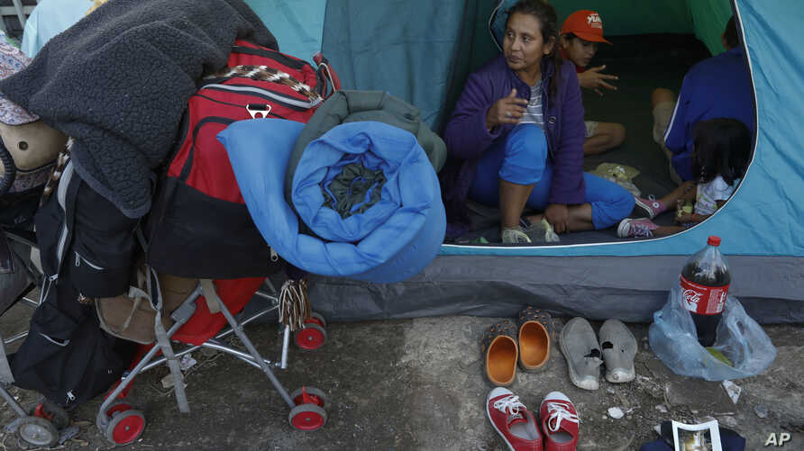 A migrant family waits in their tent on the street for buses to carry them to a new shelter, in Tijuana, Mexico, Dec. 1, 2018. Most of the thousands of migrants who had been camped out at the sports complex had agreed to move to the new, more distant