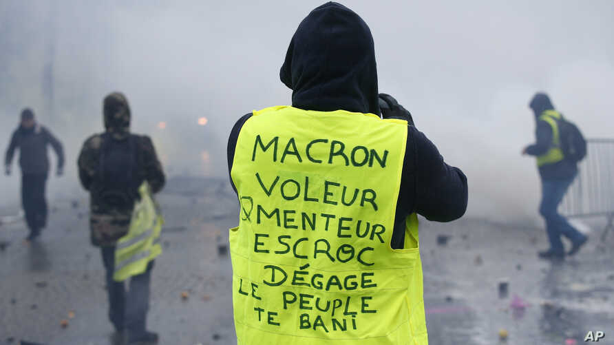 "A demonstrator wearing a yellow jacket reading ""Macron, thief, lier, crook, go away, the people banishes you"" near the Champs-Elysees avenue during a demonstration Saturday, Dec.1, 2018 in Paris."