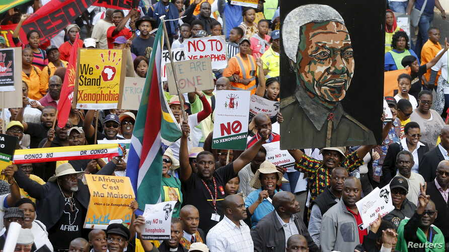 Demonstrators carry placards during a march against xenophobia in downtown Johannesburg, April 23, 2015.