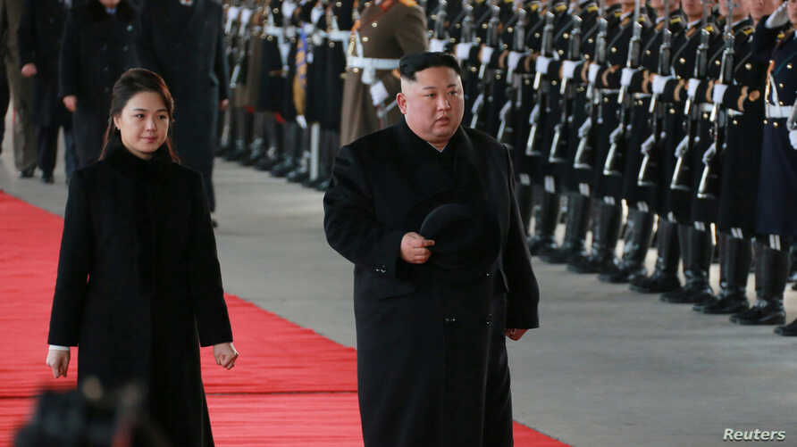 North Korean leader Kim Jong Un and wife Ri Sol Ju inspect an honour guard before leaving Pyongyang for a visit to China, this Jan. 7, 2019 photo released by North Korea's Korean Central News Agency (KCNA) in Pyongyang, Jan. 8, 2019.