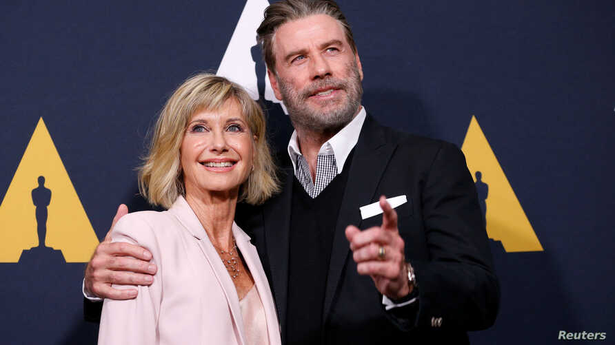 """FILE - Cast members John Travolta and Olivia Newton-John pose at a 40th anniversary screening of """"Grease"""" at the Academy of Motion Picture Arts and Sciences in Beverly Hills, California, Aug. 15, 2018."""