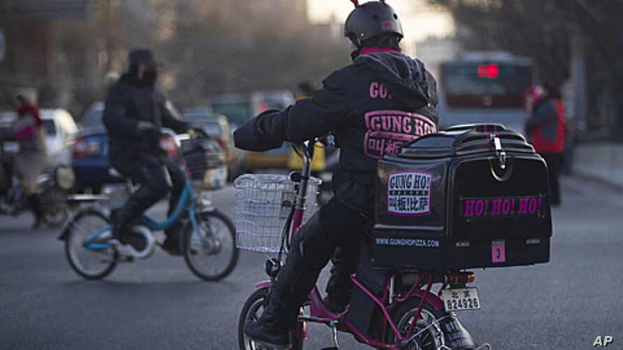 A pizza delivery man wearing a reindeer helmet rides an electric bicycle crossing a road junction in Beijing, China. Chinese leaders pledged fine-tuning to ensure stable and more balanced growth while fighting inflation, ending a top-level economic p