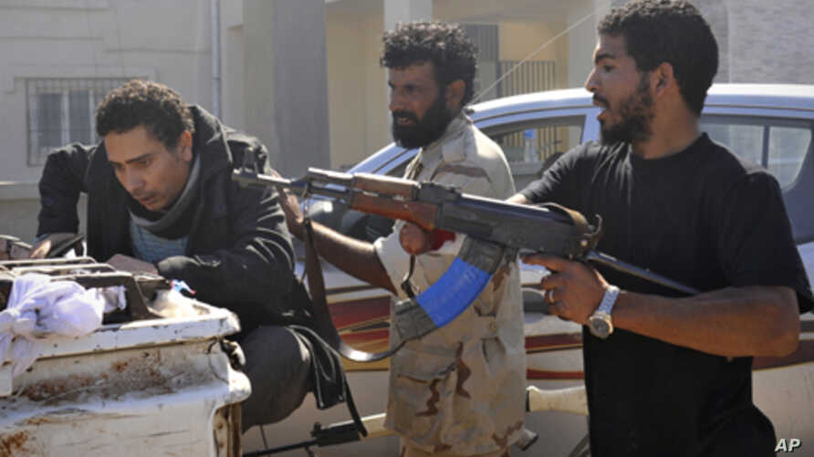 Libyan revolutionary fighters detain a suspected loyalist, left, in downtown Sirte, Libya, Wednesday, Oct. 12, 2011.