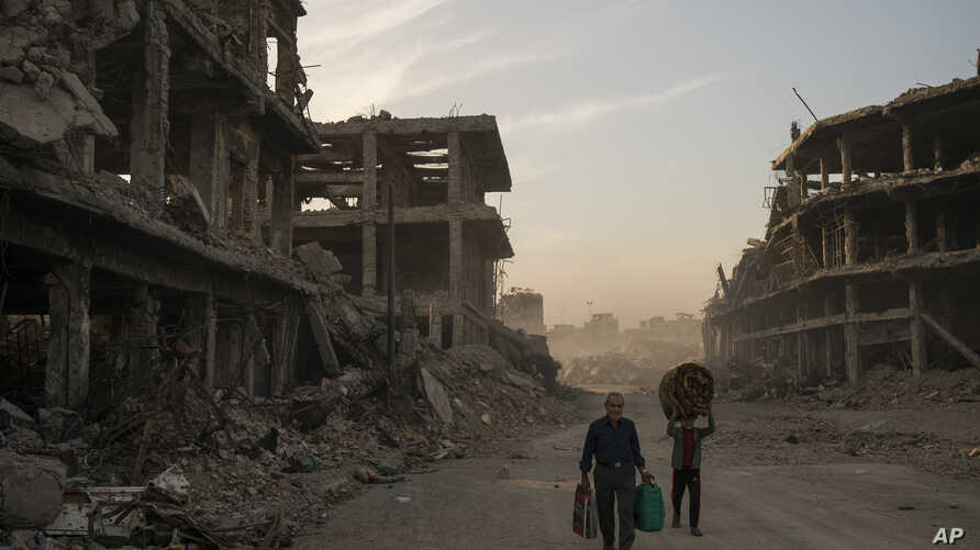 FILE -  Haider (L) and Abdullah carry belongings they collected from their damaged house to wash before returning to live in the Old City of Mosul, Iraq, Nov. 15, 2017.