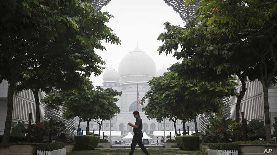 A Malaysian man walks past Palace of Justice shrouded in haze in Putrajaya, Malaysia, Sept. 11, 2015.