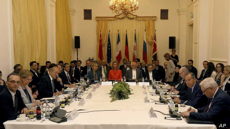 Delegates sit around a table prior to a bilateral meeting as part of the closed-door nuclear talks with Iran at a hotel in Vienna, Austria, Friday, July 6, 2018.