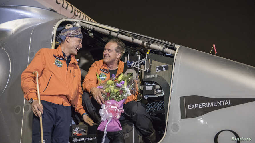 """Pilot Andre Boschberg (R) chats with pilot Bertrand Piccard after Boschberg landed """"Solar Impulse 2"""" in Muscat, Oman, March 9, 2015."""