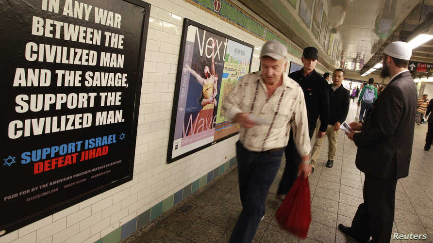 """Cyrus McGoldrick, a member of the Council on American-Islamic Relations, talks to commuters as they walk by an advertisement that reads """"Support Israel/Defeat Jihad"""" in the Times Square subway station in New York, September 24, 2012."""