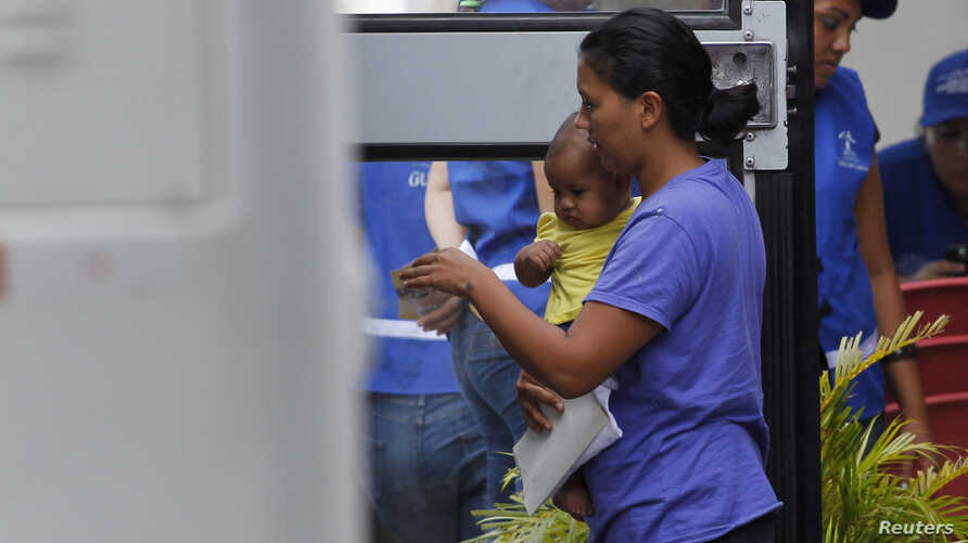A woman and her son step into a bus, bound to take deportees from U.S. to a bus station, at the international airport in San Pedro Sula, northern Honduras July 14, 2014.