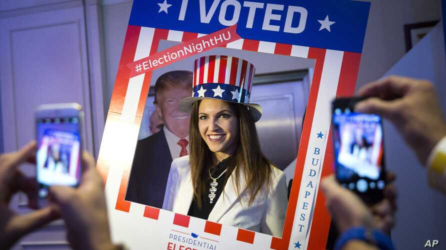 A woman wearing a US patriotic top hat poses for a photograph in the foreground of a cardboard figure depicting Donald Trump Republican presidential candidate during the Election Night Party at the US Embassy in Budapest, Hungary, Nov. 8, 2016.
