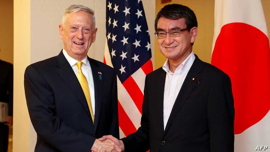 U.S. Secretary of Defense James Mattis, left, shakes hands with Japanese Foreign Minister Taro Kono at the Foreign Ministry in Tokyo, June 29, 2018.