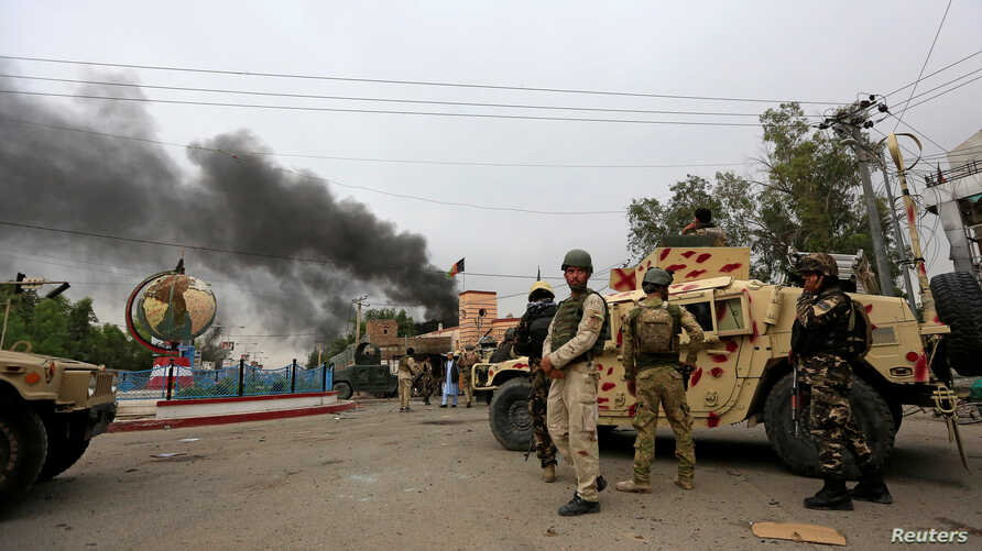 FILE - Afghan security forces keep watch at the site of an explosion in Jalalabad city, Afghanistan, May 13, 2018. On Friday three explosions rocked a cricket stadium.
