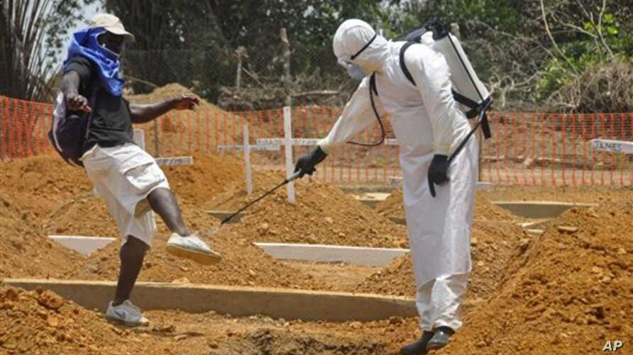 A man is sprayed with disinfectant after he celebrated the memory of a loved one who died due to the Ebola virus at a newly build grave yard for Ebola virus victims in Monrovia, Liberia, Wednesday, March 11, 2015. Liberians held a church service Wedn