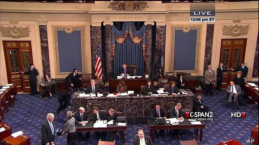This handout video image shows former Senate Majority Leader Bob Dole, right, wheeled into the Senate Chamber on Capitol Hill, Dec. 4,2012, by his wife Elizabeth Dole. Frail and in a wheelchair, Dole was a startling presence on the Senate floor as la