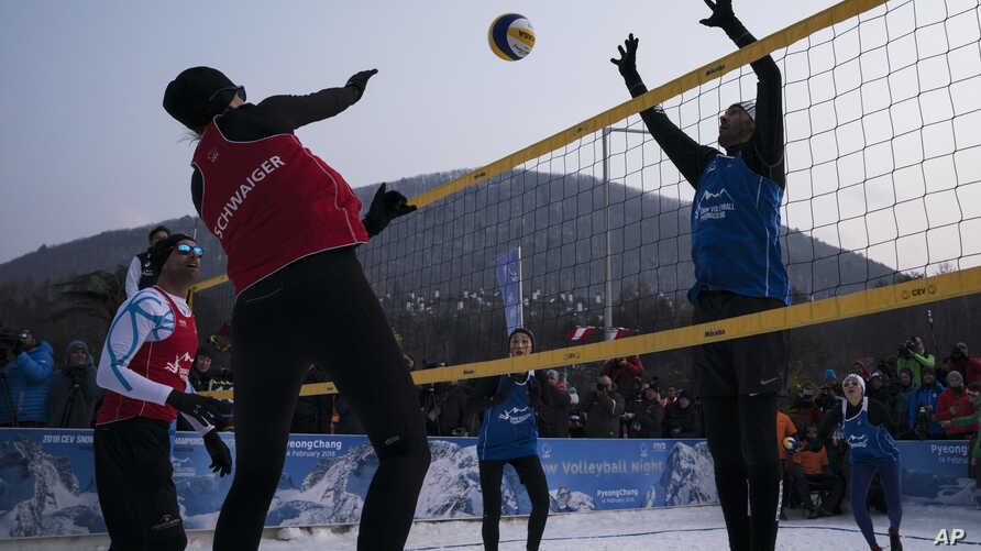 FILE - Brazil's Giba, right, tries to block Austria's Stefanie Schwaiger during a snow volleyball exhibition match at the Austria House in Pyeongchang, South Korea, Feb. 14, 2018.