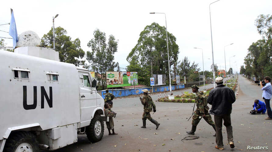 Congolese Revolution Army (CRA) rebels walk past a United Nations patrol truck parked along a street in Goma in the eastern Democratic Republic of Congo (DRC), November 20, 2012.