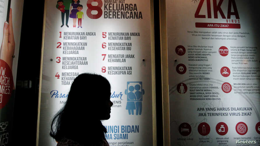 A woman passes a poster explaining about the Zika virus at the Ministry of Health office in Jakarta, Indonesia, September 2, 2016. Vietnam's health ministry announced November 2, 2016, a large increase of Zika cases.