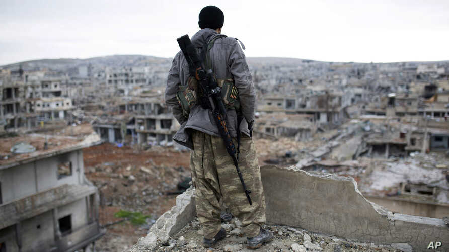 FILE - A Syrian Kurdish sniper looks at the rubble in the Syrian city of Kobani.