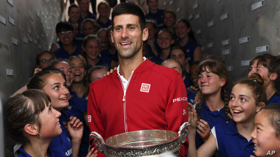 Serbia's Novak Djokovic is cheered by ball girls after defeating Britain's Andy Murray in their final match of the French Open tennis tournament at the Roland Garros stadium, June 5, 2016 in Paris.