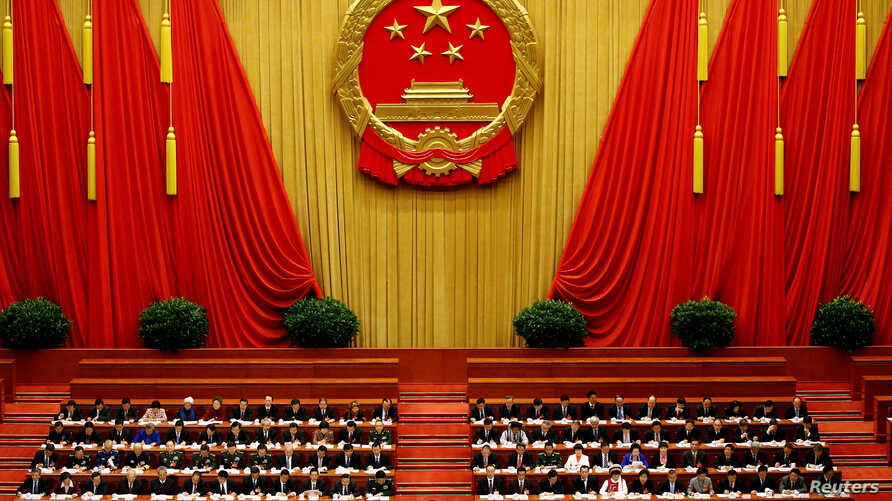 China's President Xi Jinping and other delegates listen as China's Premier Li Keqiang (not pictured) delivers a government work report during the opening session of the National People's Congress (NPC) at the Great Hall of the People in Beijing, Chin