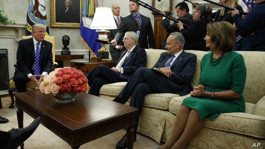 President Donald Trump speaks to, from left, Senate Majority Leader Mitch McConnell, R-Ky., Senate Minority Leader Chuck Schumer, D-N.Y., and House Minority Leader Nancy Pelosi, D-Calif., during a meeting with Congressional leaders in the Oval Office...