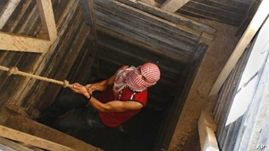 A Palestinian smuggler uses a rope to climb out of a tunnel linking the southern Gaza Strip town of Rafah with Egypt, 10 Dec 2009