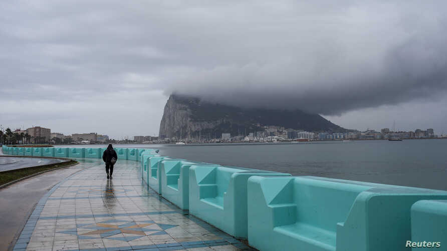 A pedestrian walks along the seafront in front of the Rock of Gibraltar as seen from La Linea de la Concepcion, Spain, Nov.22, 2018.