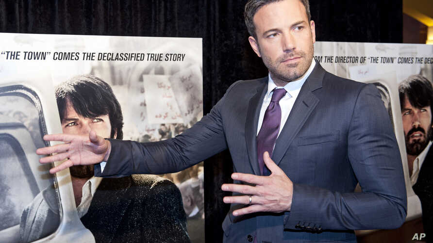 Director and actor Ben Affleck plays around while posing for photographers at the premiere of his film Argo in Washington, Wednesday, Oct. 10, 2012.