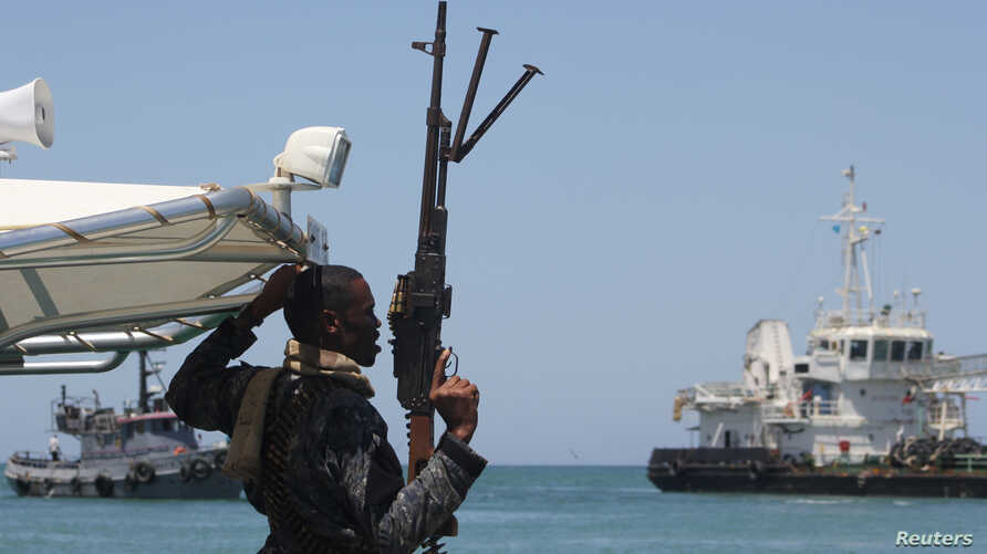 FILE - A maritime policeman on a tag-boat guards oil tanker Aris-13, which was released by pirates, as it sails to dock on the shores of the Gulf of Aden in the city of Bosasso, northern Somalia's semi-autonomous region of Puntland, March 19, 2017.