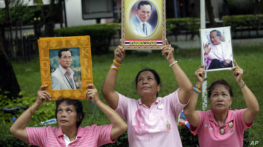 Thais hold portraits of Thai King Bhumibol Adulyadej at Siriraj Hospital where the king is being treated in Bangkok, Thailand, Oct. 11, 2016.