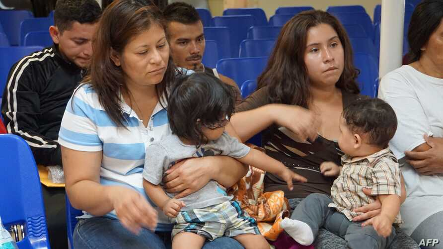 FILE - Mothers and children wait to be assisted by volunteers in a humanitarian center in the border town of McAllen, Texas,  June 15, 2018.