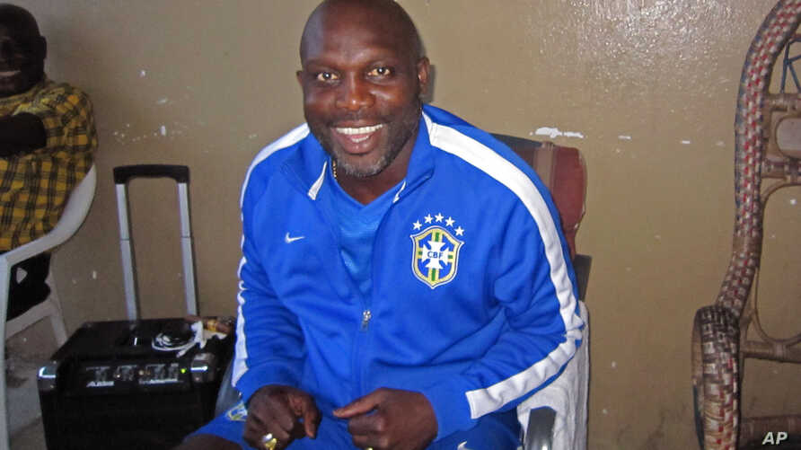FILE - Liberian soccer star George Weah smiles inside a room in Monrovia, Liberia, Aug. 10,  2014.
