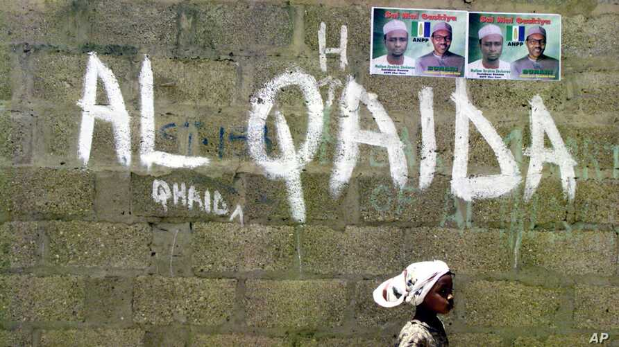 FILE - A girl walks past a wall with graffiti about the al-Qaida network in Kano, Nigeria, April 18, 2003. An airstrike this week by U.S. forces and the Libyan government targeted Al-Qaida in the Islamic Maghreb, southeast of Bani Walid, Libya.