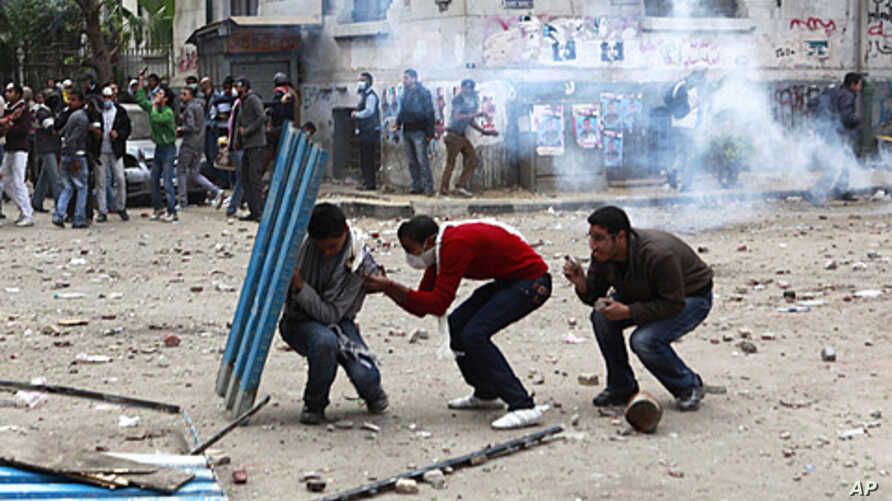 Protesters hide behind a portion of a fence as police fire tear gas and throw stones back at protesters, who have been throwing stones at the police, near Tahrir Square in Cairo Egypt, November 20, 2011.