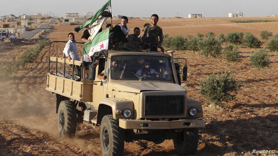 Free Syrian Army fighters with opposition flags ride a truck, which they say was captured from the Syrian army loyal to President Bashar al-Assad, in Saraqeb near Idlib October 15, 2012.