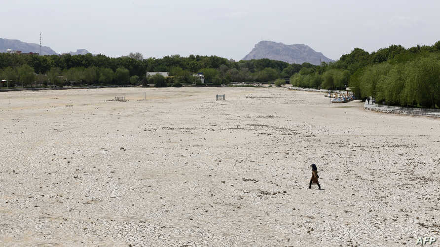 An Iranian girl walks across the Zayandeh Rud river in Isfahan, now dry because of water extraction before it reaches the city, April 11, 2018.