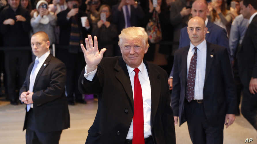 President-elect Donald Trump waves to the crowd as he leaves the New York Times building following a meeting, Nov. 22, 2016, in New York.