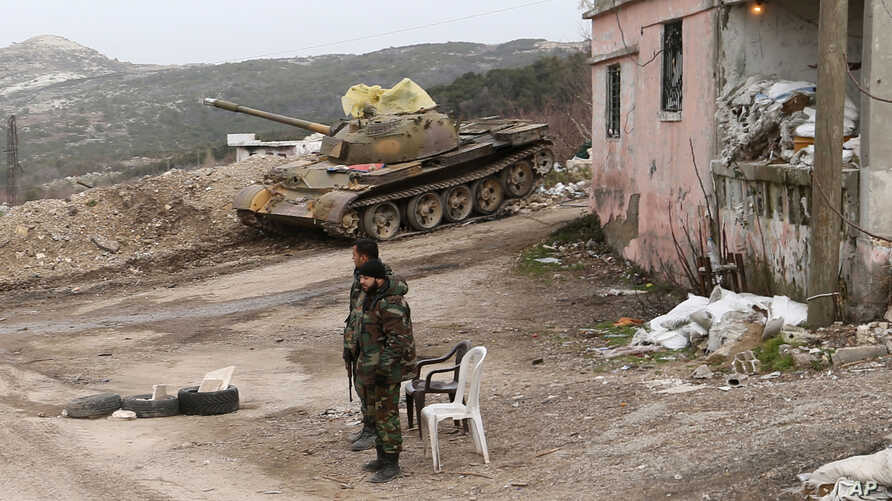 Syrian troops stand, with a destroyed tank in the background, on a street in Salma, Syria, Jan. 22, 2016. Syrian government forces, relying on Russian air cover, have recently seized Salma, located in Syria's province of Latakia, from militants.