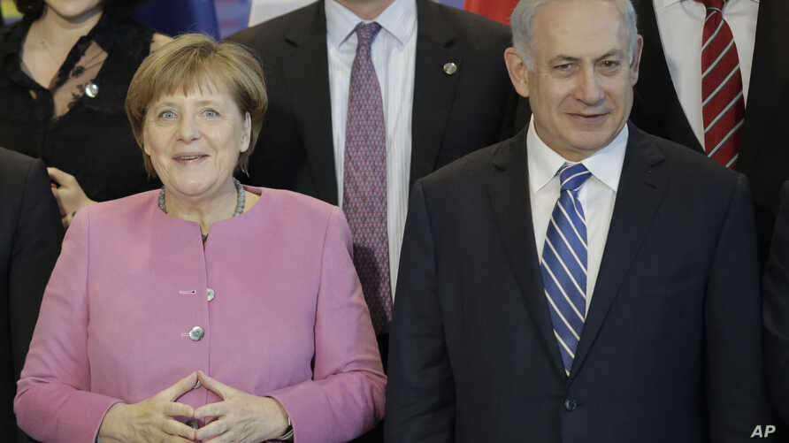 German Chancellor Angela Merkel, left, and the Prime Minister of Israel Benjamin Netanyahu, right, pose with government members for a group photo during a one day German-Israeli governmental meeting at the chancellery in Berlin, Germany, Feb. 16, 201