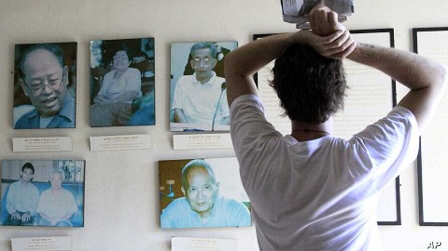 Tourist looks at portraits of former Khmer Rouge leaders Ieng Sary (R), 84, ex-foreign minister, his wife Ieng Thirith, 78, former minister of social welfare (2nd L), former prison chief Kaing Guek Eav (R), better known as Duch, former President Khie