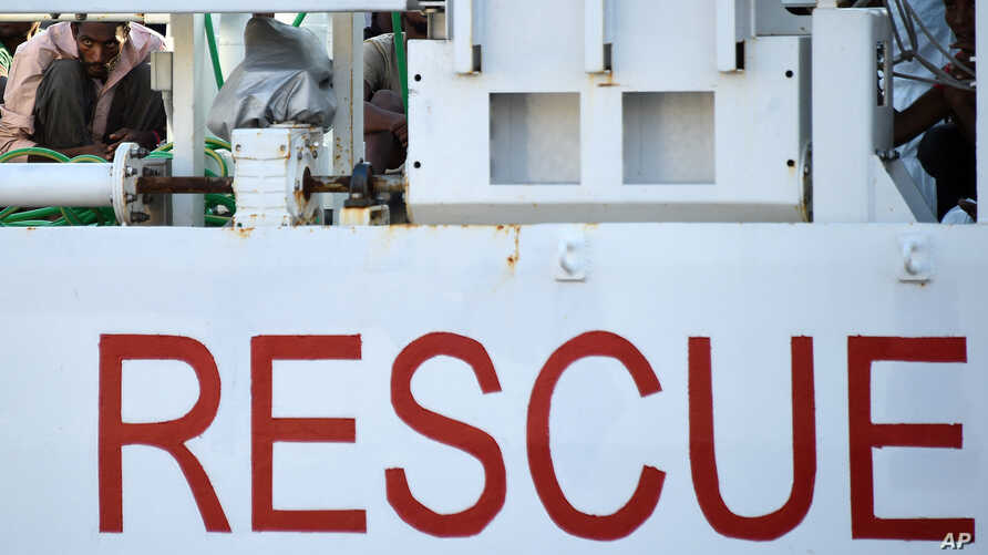 FILE -- Migrants wait to disembark from Italian Coast Guard ship in Sicily, Italy, Aug. 29, 2015. The Italian Coast Guard rescued nearly 6,000 migrants in one day from the sea October 3, 2016.