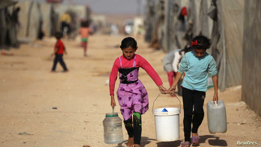 Internally displaced Syrian girls carry water containers in Jrzinaz camp in the southern part of Idlib, Syria, June 21, 2016. (Reuters)