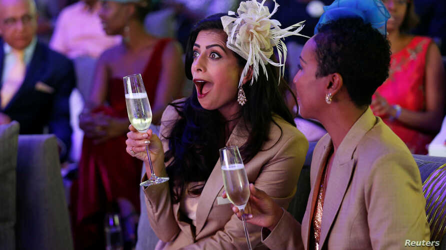 Pinky Ghelani and Suzzy Wokabi watch a TV broadcast of Britain's Prince Harry and Meghan Markle's royal wedding at the Windsor golf and country club in Nairobi, Kenya, May 19, 2018.