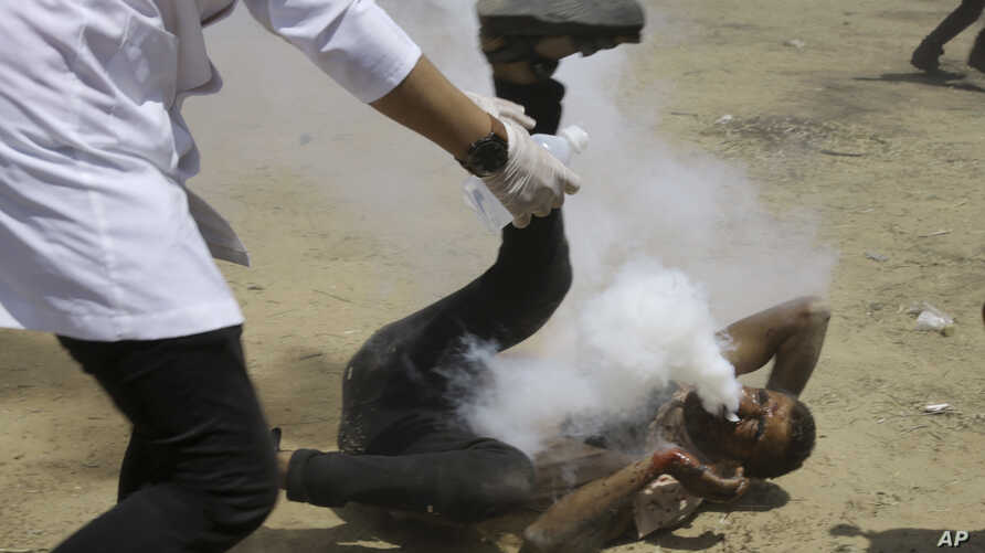 Palestinian medic rushes to a a protester who got shot in his mouth by teargas canister fired by Israeli troops near the Gaza Strip's border with Israel, east of Khan Younis, in the Gaza Strip, Friday, June 8, 2018. Thousands of Palestinians are stre